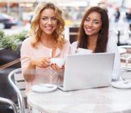 两台美丽的女孩杯子和膝上型计算机 免版税库存照片