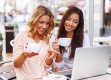 两台美丽的女孩杯子和膝上型计算机 免版税图库摄影