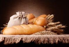 面包、面粉大袋和耳朵束起静物画 免版税库存图片
