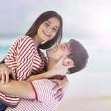 获得的夫妇在海滩的乐趣 库存图片