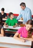 Δάσκαλος και έφηβος που εξετάζουν μεταξύ τους Στοκ Εικόνες