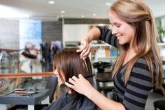 美发师切口客户的头发 免版税库存照片