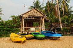 与椰子树、小屋和床的热带海滩设置。 库存图片