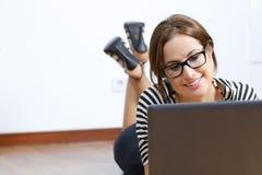 浏览膝上型计算机的一名美丽的妇女的画象说谎在地板上 免版税图库摄影