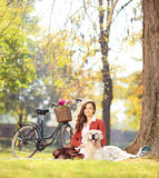 在一棵草的美好的女性开会与她的狗在公园 免版税库存图片
