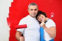 夫妇绘画墙壁红色 免版税库存照片