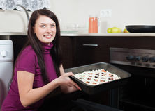 把鱼饼放的妇女在烧烤平底锅上入烤箱 免版税图库摄影