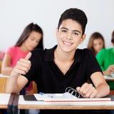 打手势赞许的少年男小学生在教室 免版税库存照片