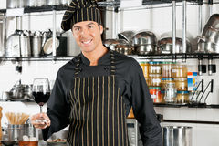 拿着杯红葡萄酒的厨师 免版税图库摄影