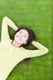 说谎在草原的微笑的妇女 免版税库存照片