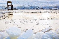 在冰孔附近的冰封椅子在冻湖 库存图片