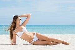 晒日光浴在海滩的妇女 免版税图库摄影