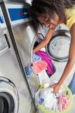 装载肮脏的衣裳的妇女在洗衣机 免版税库存照片