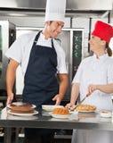 准备甜盘的愉快的厨师在厨房里 免版税库存照片