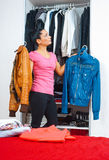 Ελκυστική γυναίκα μπροστά από το σύνολο ντουλαπιών των ενδυμάτων Στοκ Φωτογραφία