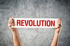拿着与革命标题的人白色横幅 免版税库存照片