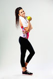 年轻愉快的体育妇女用苹果和瓶水 免版税图库摄影