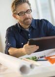 使用片剂计算机的建筑师在书桌 图库摄影