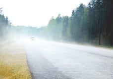 有汽车的有雾的路 库存照片