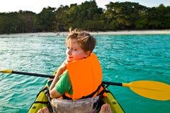 男孩在独木舟用浆划在海洋 库存照片