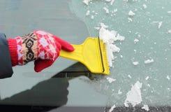 妇女刮的冰的手从汽车挡风玻璃的 库存照片