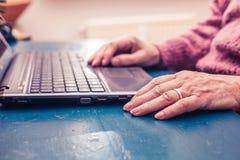 在家研究便携式计算机的老妇人 免版税库存照片