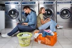 使用膝上型计算机和耳机的夫妇在洗衣店 库存照片