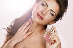 应用香水的一名美丽的妇女的特写镜头 免版税库存照片