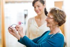 拿着新的玻璃的资深妇女在商店 免版税库存图片