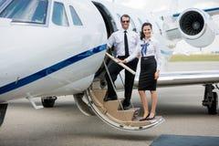 站立在私人喷气式飞机的空中小姐和飞行员 免版税库存照片