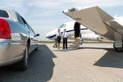 站立整洁的大型高级轿车的空中小姐和飞行员和 库存图片
