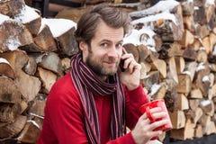 愉快的人谈话在一个手机室外在冬天期间 免版税库存照片