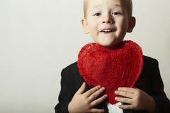 有红色心脏的微笑的孩子。有心脏标志的滑稽的男孩。可爱的孩子在母亲的黑衣服情人节 免版税库存照片