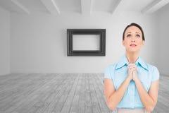 混乱的年轻女实业家祈祷 库存照片