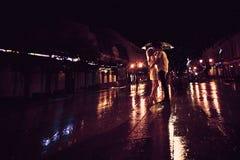 爱在亲吻的夫妇雨/剪影在伞下 库存照片