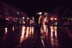 爱在亲吻的夫妇雨/剪影在伞下 免版税库存图片