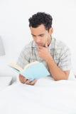 严肃的年轻人阅读书在床上 库存照片