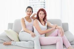 坐在客厅的两个严肃的美丽的女性朋友 免版税图库摄影