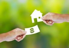 有纸币和房子形状的手 免版税库存图片