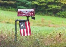 与古色古香的旗子的老农村邮箱 免版税库存照片