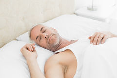 在家睡觉在床上的成熟人 免版税库存图片