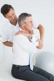 审查成熟人的男性按摩医生 免版税库存照片
