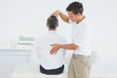 审查成熟人的男性按摩医生 免版税库存图片