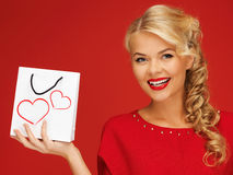 红色礼服的可爱的妇女有购物袋的 免版税库存图片