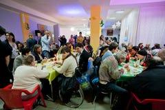 可怜的人民在桌附近坐用食物在无家可归者的圣诞节慈善晚餐 免版税库存照片