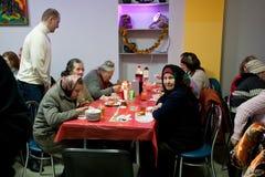 年长可怜的妇女食用食物在无家可归者的圣诞节慈善晚餐 免版税图库摄影