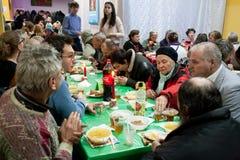 年长妇女和人食用食物在无家可归者的圣诞节慈善晚餐 免版税库存照片