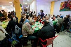无家可归和不健康的人民吃食物在无家可归者的圣诞节慈善晚餐 免版税库存照片