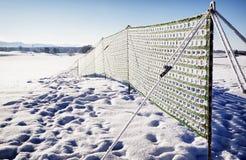 反对随风飘飞的雪的篱芭 免版税库存照片
