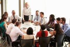 女实业家发言在会议室表附近 免版税图库摄影